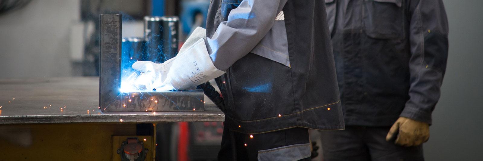 Un homme regarde un soudeur portant des gants de protection et un bleu de travail.