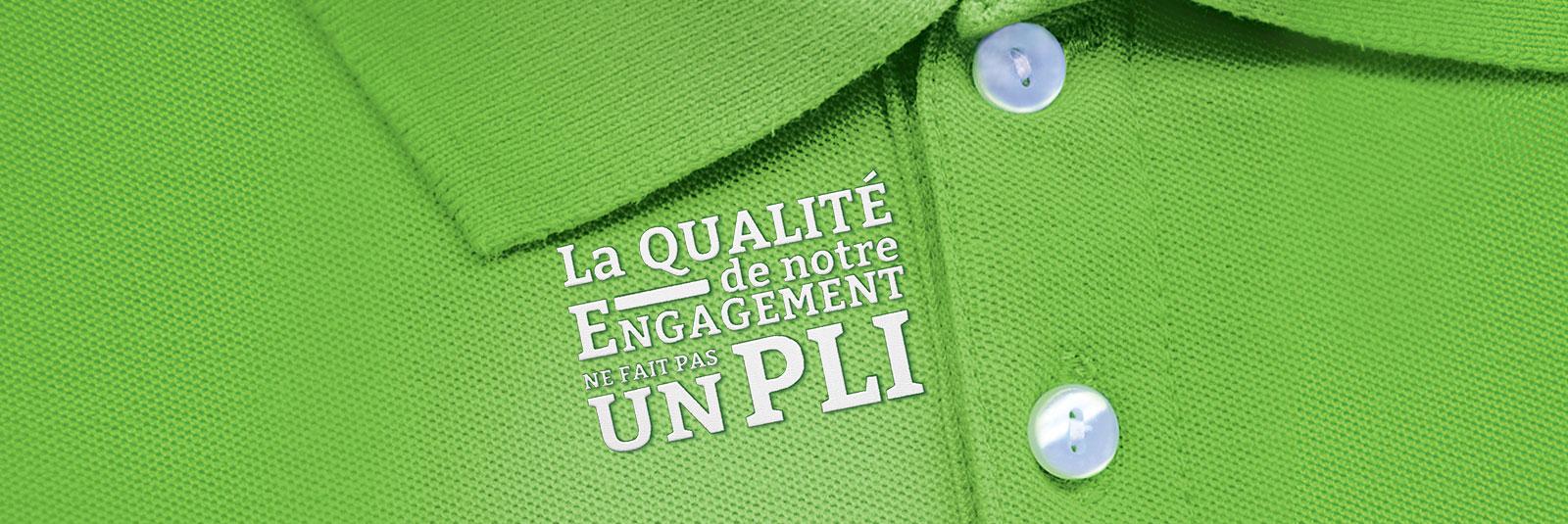 """Polo vert avec deux boutons. A gauche de la boutonnière il est inscrit """"La qualité de notre engagement ne fait pas un pli""""."""