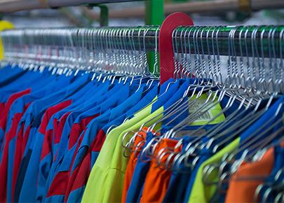 Cintres sur des portants. Des vêtements pour professionnels sont accrochés suite à l'entretien du linge par la marque Anett.