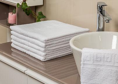 Pile de serviettes à côté d'un lavabo, c'est du linge éponge proposé à la location et l'entretien par la marque Anett.