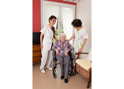 Deux aide-soignante prennent soin d'une personne âgée. Elles portent des blouses pour infirmières de la gamme woody par Anett.